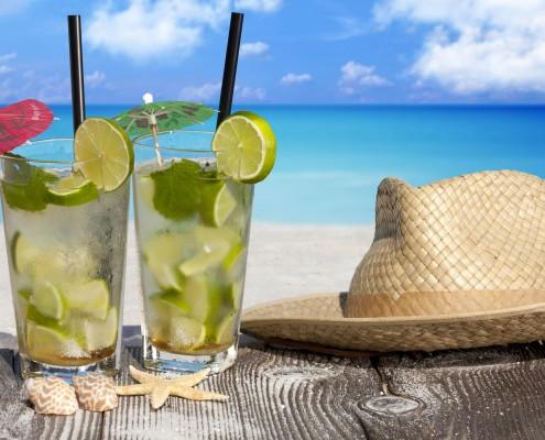 Erfrischende Mojito Cocktails und ein Strohhut